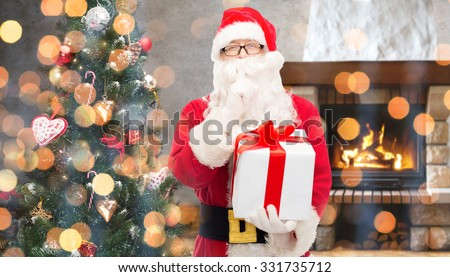 christmas, winter, holidays and people concept - man in costume of santa claus with gift box and tree making hush gesture over home fireplace and lights background - stock photo