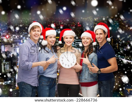 christmas, winter, holidays, time and people concept - group of smiling teenagers in santa helper hats with clock pointing finger over snowy night city background - stock photo