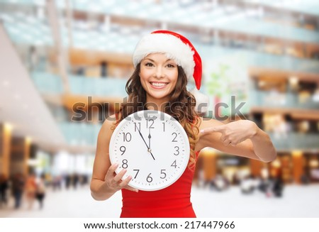 christmas, winter, holidays, time and people concept - smiling woman in santa helper hat and red dress with clock over shopping center background - stock photo