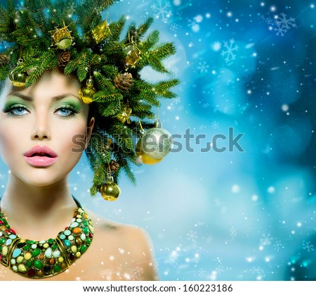 Christmas Winter Woman. Beautiful New Year and Christmas Tree Holiday Hairstyle and Make up. Beauty Fashion Model Girl over Snow Background with Snowflakes. Creative  Hair style decorated with Baubles - stock photo