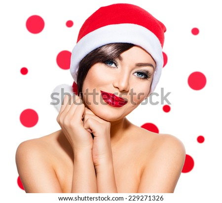 Christmas Woman. Beauty Model Girl in Santa Hat isolated on White Background. Holiday make up. Funny Smiling Surprised Woman Portrait. Red Lips and Manicure. Beautiful Holiday Makeup - stock photo