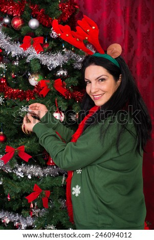 Christmas woman decorates her tree with snowflakes and wearing reindeer ears - stock photo