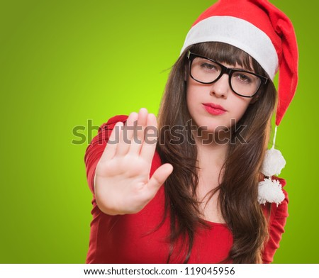 christmas woman doing a stop gesture against a green background - stock photo