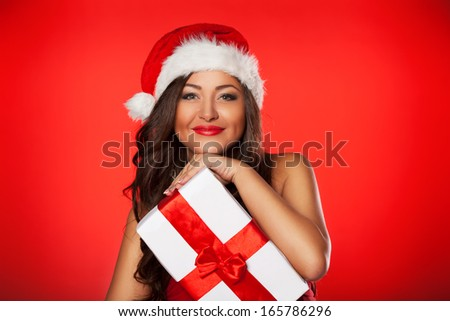 Christmas woman holding christmas gifts smiling. Cute beautiful Caucasian  santa girl isolated on red background - stock photo