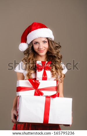 Christmas woman holding presents excited. Young happy woman wearing santa hat looking to side showing Christmas gift isolated. Beautiful young santa woman.