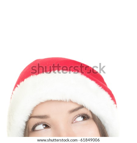 Christmas woman looking upwards at copy space. Closeup of santa girl looking up at white space. Mixed Asian / Caucasian woman. - stock photo