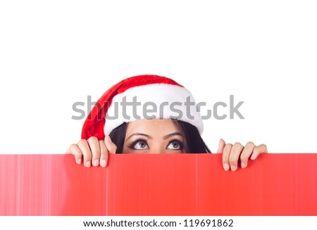 Christmas woman peeking over edge of red billboard and looking up with copy space - stock photo