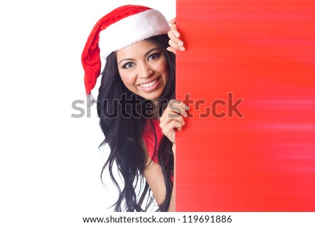 Christmas woman peeking over edge of red billboard with copy space - stock photo
