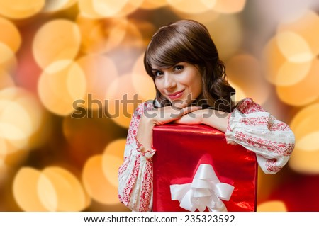 Christmas woman portrait hold red christmas gift over isolated christmas colorful lights background - stock photo