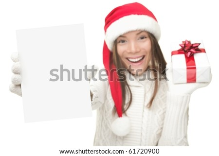 Christmas woman showing blank sign with empty copy space. Beautiful young smiling woman in Santa hat holding white paper card. Caucasian / Asian model isolated on white background. Shallow DOF. - stock photo