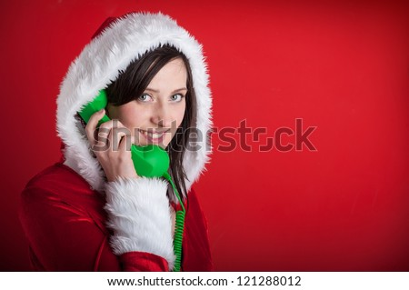 Christmas woman talking at the phone on red background. Listening to special gift orders. - stock photo