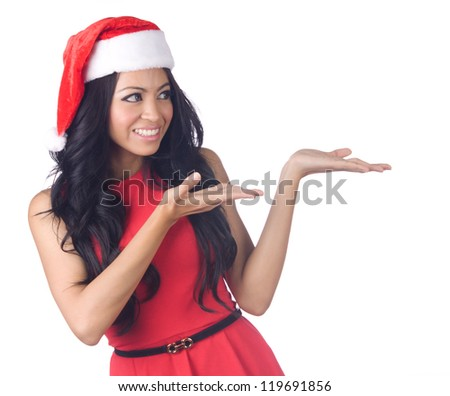 Christmas woman wearing a santa hat smiling and  presenting isolated on white background - stock photo