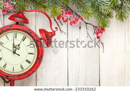 Christmas wooden background with fir tree and antique alarm clock. View from above with copy space - stock photo