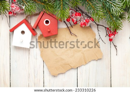Christmas wooden background with fir tree and birdhouse decor. View from above with paper for copy space - stock photo