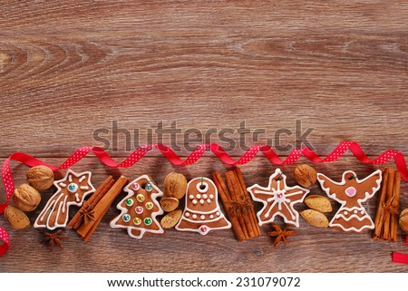 christmas wooden background with homemade gingerbread cookies ,spices and red ribbon  - stock photo