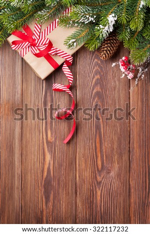 Christmas wooden background with snow fir tree, alarm clock and gift box. View with copy space - stock photo