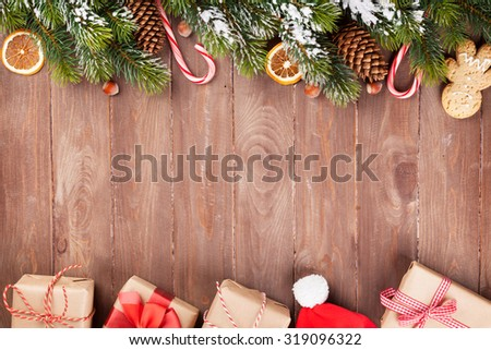 Christmas wooden background with snow fir tree, decor and gift boxes - stock photo