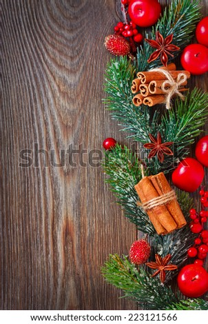 Christmas wooden background with spices and Christmas ornament. - stock photo