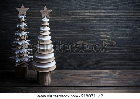 Christmas wooden trees over dark rustic wooden background. Eco style, natural wood, space for text. Toned image
