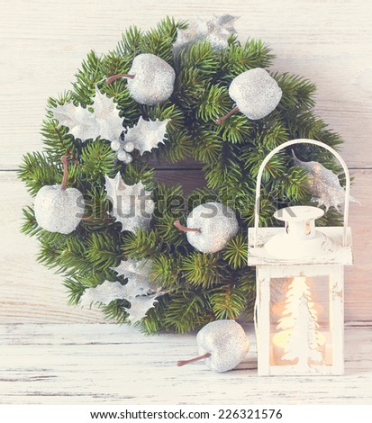 Christmas wreath and candle lantern on an old wooden background. Toned photo. - stock photo