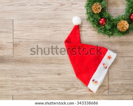 Christmas wreath and   Santa claus hat  on wooden background ( Composition and space for text ) - stock photo