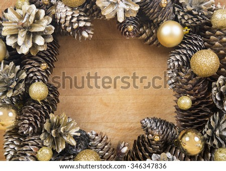 Christmas wreath of cones and gold balls close-up on wooden background.