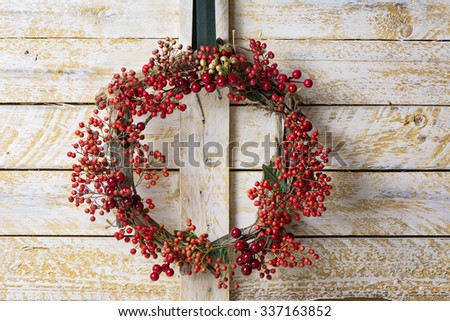 Christmas wreath of evergreen and berries on wooden background. Natural Nandian network and rustic wood crown