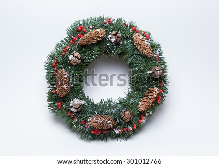 Christmas wreath of fir branches decorated with ilex, cypress cones, pine cones and artificial snow on white background - stock photo