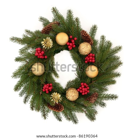 Christmas wreath of pine fir with red holly berry clusters, pine cones and golden bauble decorations isolated over white background. - stock photo