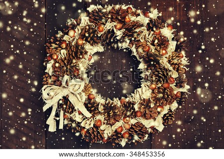 Christmas wreath on a rustic wooden door.  Hand made from organic elements. Magic snowfall in front. Christmas background. Close up. Toned  - stock photo