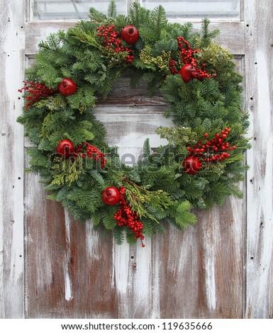 Christmas wreath on a rustic wooden front door. - stock photo