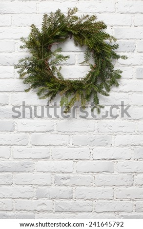 Christmas wreath on a white brick wall - stock photo