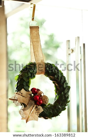 Christmas wreath on the glass door in shop. - stock photo