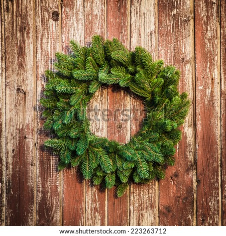 Christmas wreath on the shabby wooden door. Christmas holiday background with copy space - stock photo
