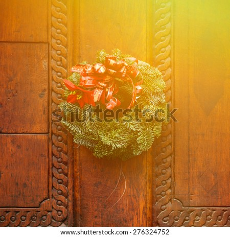 Christmas wreath on wooden door decoration - stock photo