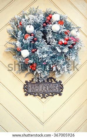 Christmas wreath on wooden door decoration. - stock photo