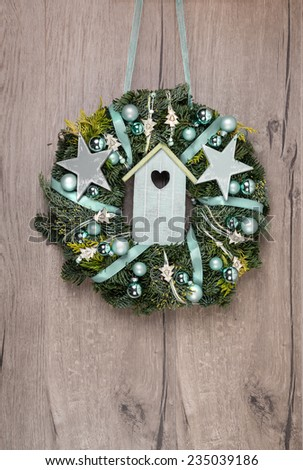 Christmas wreath on wooden door with green decorations, space for your text  - stock photo
