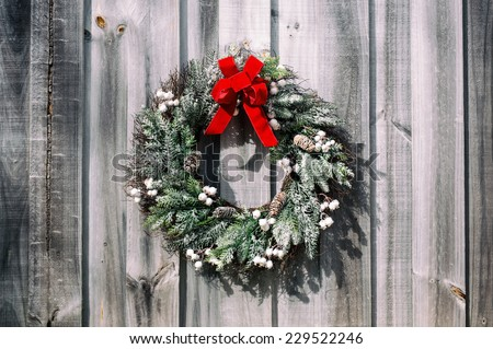 Christmas wreath sprinkled with snow made of pine branches, berries and pine cones with a red velvet bow hangs on a weathered plank wall.  Vintage filter applied.  - stock photo
