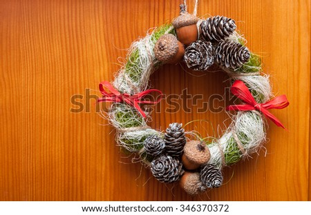 Christmas wreath with acorns, pine cones and red bows. On wooden background. - stock photo