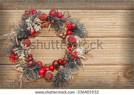 Christmas wreath with decorations on the wooden background. - stock photo