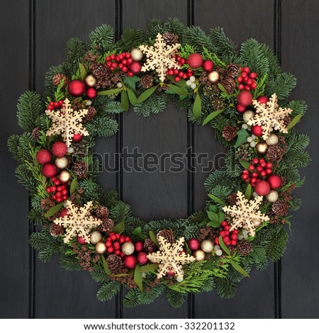 Christmas wreath with gold snowflake bauble decorations, holly, mistletoe and winter greenery over dark oak front door background. - stock photo