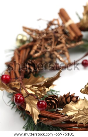 Christmas wreath with golden holly leaves, cones, red berries and cinnamon on white background. Shallow dof - stock photo
