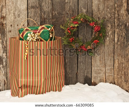 Christmas wreath with natural decorations hanging on a rustic wooden wall beside a colorful bag filled with Christmas gifts. - stock photo