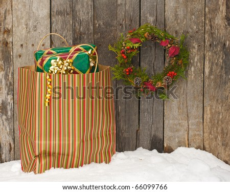 Christmas wreath with natural decorations hanging on a rustic wooden wall with a bag of gifts in the snow. - stock photo