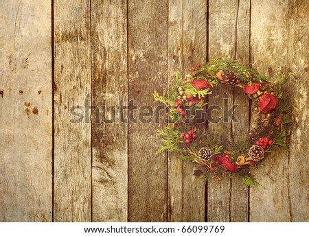Christmas wreath with natural decorations hanging on a rustic wooden wall with copy space.  Grunge textured. - stock photo