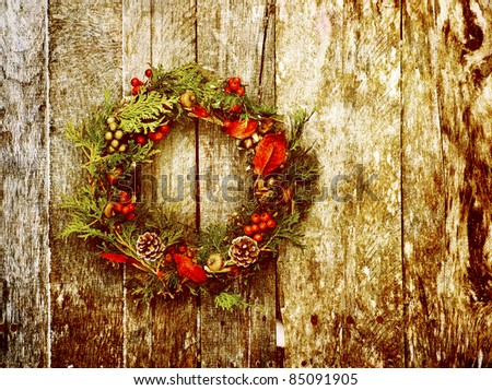Christmas wreath with natural decorations hanging on a rustic wooden wall with copy space.  Heavily textured. - stock photo