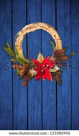 Christmas wreath with poinsettia on the old blue wooden doors - stock photo