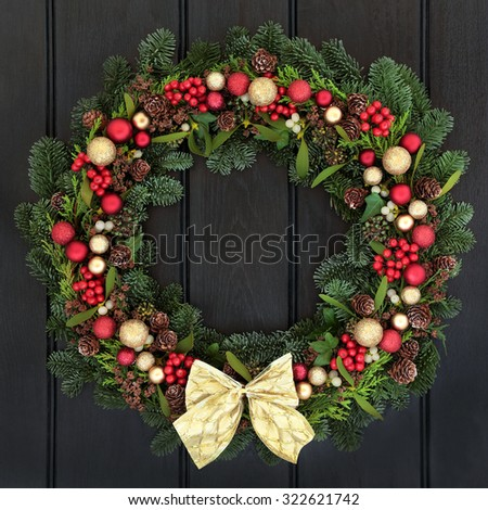 Christmas wreath with red and gold bauble decorations, bow, holly, mistletoe, pine cones and blue spruce fir over dark wood front door background. - stock photo