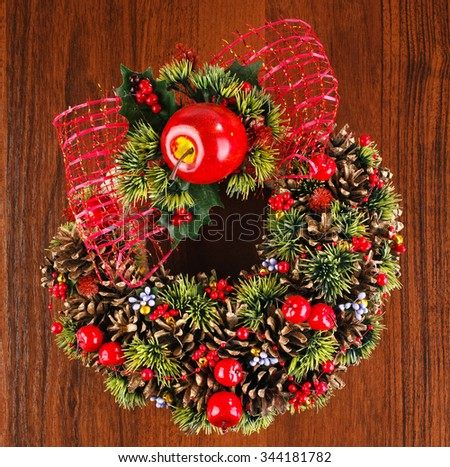 Christmas wreath with red and gold bauble decorations, bow, holly, mistletoe, pine cones and blue  on wooden background, place for text