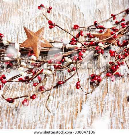 Christmas wreath with red and white berries and rusty metal stars on wooden background. Falling snow effect. Square image. Vintage Style - stock photo